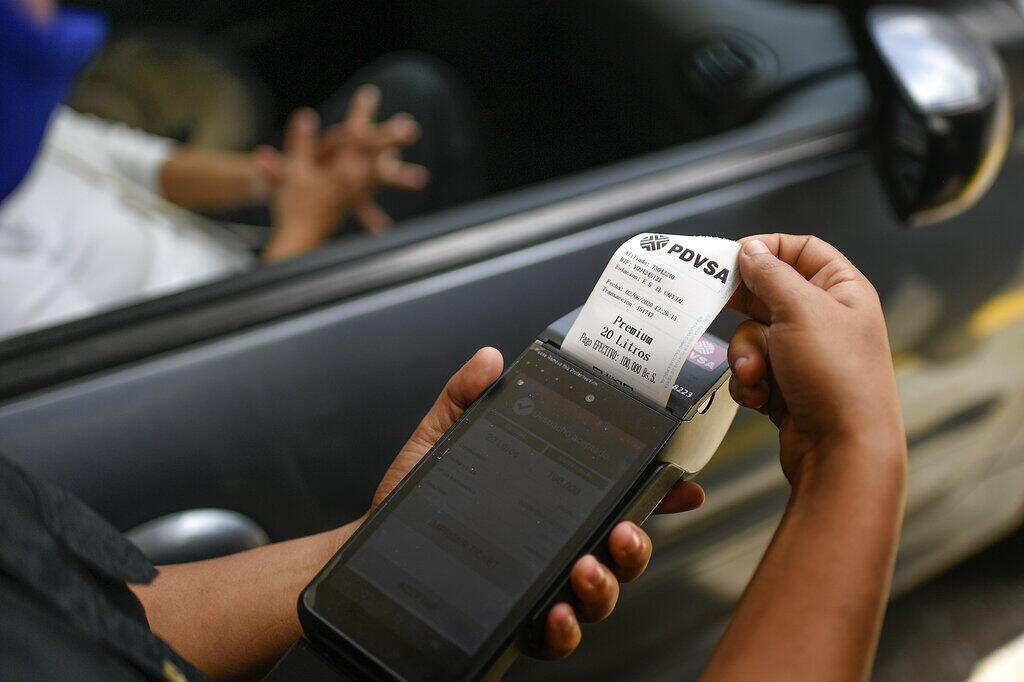 Una máquina biométrica imprime un vale en una gasolinera de una compañía petrolera estatal en Caracas, Venezuela, el martes 2 de junio de 2020. A partir de junio, a los venezolanos se les permite 120 litros de combustible subsidiado por mes, que es monitoreado por cada individuo a través de una máquina biométrica usando la huella digital de la persona. Después de sus primeros 120 litros, sin embargo, tienen que pagar precios internacionales por su combustible. (AP Photo/Matias Delacroix)