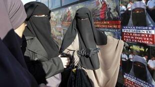 Hind Ahmas (à direita), uma das mulheres condenada a pagar multa pelo uso do niqab, o véu islâmico integral.
