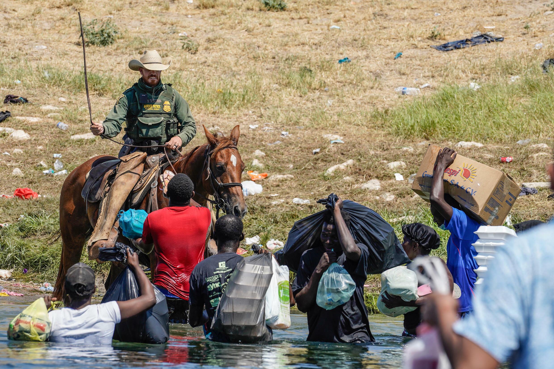 Un agente de la Patrulla Fronteriza de Estados Unidos a caballo utiliza sus riendas mientras intenta impedir que migrantes haitianos entren en un campamento a orillas del Río Grande, cerca del puente internacional Acuña del Río, en Del Río, Texas