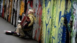 Homem toca instrumento nas ruas de Paris.