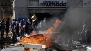 Uma barricada em chamas bloqueia uma rua enquanto manifestantes protestam contra o governo do Chile em Concepción, Chile, 6 de novembro de 2019.