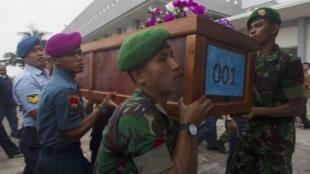 Militares indonésios carregam caixão com corpo de vítima do acidente aéreo da companhia AirAsia, nesta quarta-feira, 31 de dezembro de 2014.