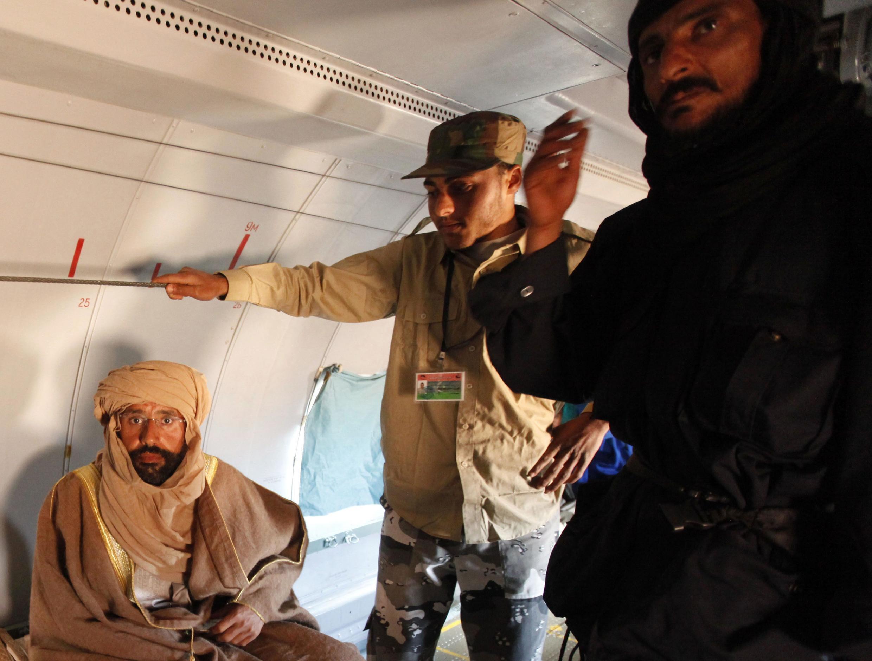 Сейф аль-Ислам Каддафи (слева) в самолете после его поимки 19/11/2011