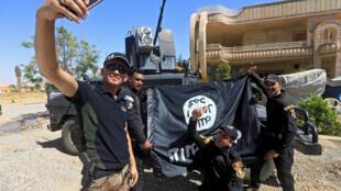 Miembros del ejército iraquí se retratan delante de una bandera del grupo Estado Islámico, tras la batalla en Mosul oeste.