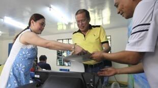 Le président philippin Benigno Aquino (au centre) vote le 13 mai à Tarlac dans le nord du pays.