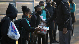 Students have their hands sanitised as they return to the Melpark Primary School in Johannesburg, South Africa.