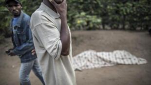 Des hommes près du corps de l'une des six personnes tuées le 1er juillet, lors d'une précédente opération de la police burundaise à Bujumbura dans le quartier de Mutakura.