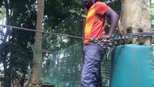 Un jeune Ivoirien en pleine activité d'accrobranche (balade dans les arbres) en banlieue d'Abidjan en Côte d'Ivoire.