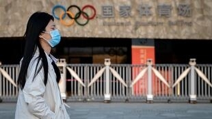 Passers-by at Beijing's Olympic Park wear protective face masks as the coronavirus pandemic causes problems around the world