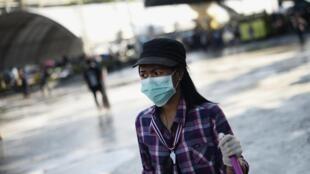 Une manifestante opposée au gouvernement nettoie les rues à la veille des cérémonies en hommage au roi, à Bangkok, ce mercredi 4 décembre.