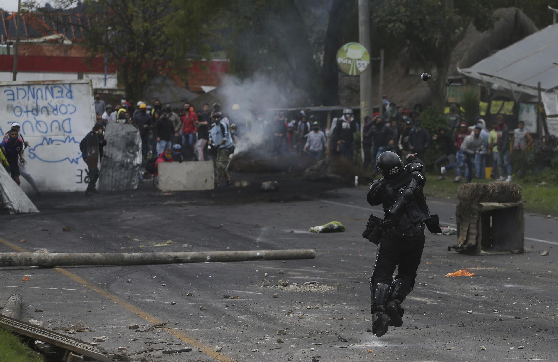 Un policía lanza una granada aturdidora a los manifestantes antigubernamentales durante los enfrentamientos con la policía en Gachancipa, Colombia, el viernes 7 de mayo de 2021.