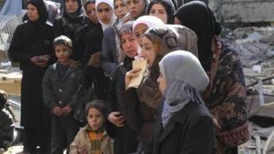 Palestinos esperam ajuda da ONU no campo de refugiados de Yarmuk, perto de Damasco, capital da Síria.