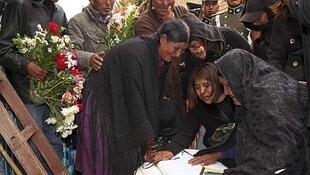 Familiares del policía Reynaldo Quispe llojan junto a su féretro en el Cementerio General de La Paz, el 21 de octubre de 2013.