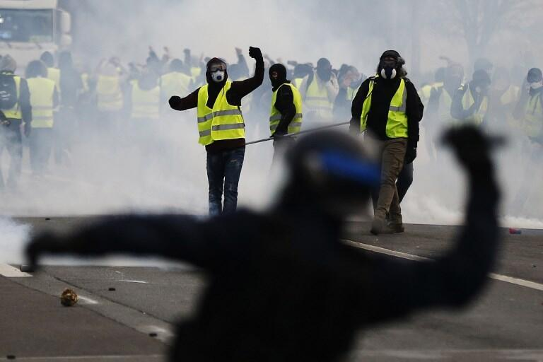 Protestors wearing a yellow vest (gilet jaune), clash with French riot police during a demonstration against rising costs of living they blame on high taxes in Mondeville near Caen, northwestern France, on December 8, 2018.