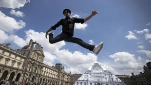 O francês JR expõe sua arte na pirâmide externa do Museu do Louvre.