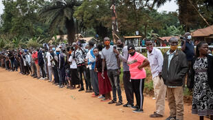 Voters wait in a line and look back as Bobi Wine arrives at a polling station in Magere, Uganda on 14 January 2021.