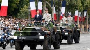 امانوئل ماکرون، رئیس جمهوری فرانسه، در کنار فرمانده ارتش این کشور در حال ساندیدن از نیروهای نظامی مستقر در خیابان شانزلیزه پاریس در روز سالگرد انقلاب فرانسه. یکشنبه ٢٣ تیر/ ١٤ ژوئیه ٢٠۱٩
