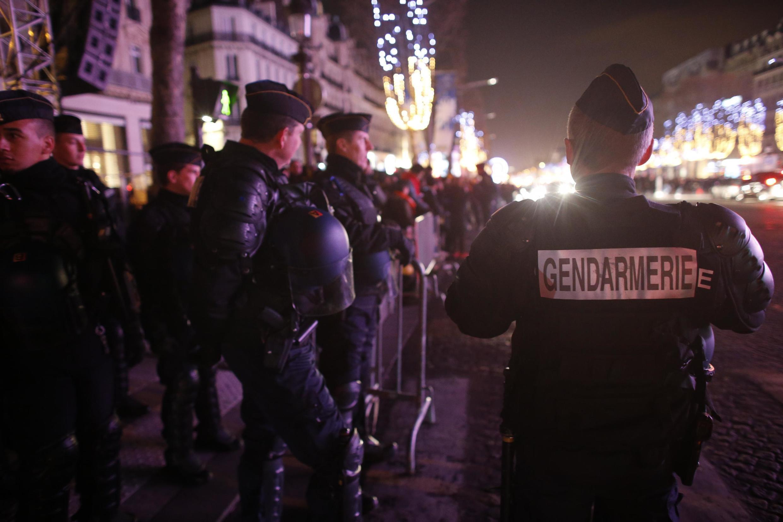 French gendarmes patrol at the Avenue des Champs-Élysées boulevard in Paris on New Year's Eve, December 31, 2015.