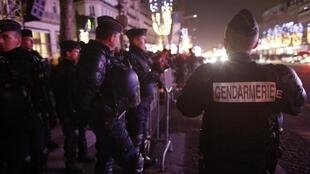 French gendarmes patrol at the Avenue des Champs-Élysées boulevard in Paris on New Year's Eve, December 31, 2015.