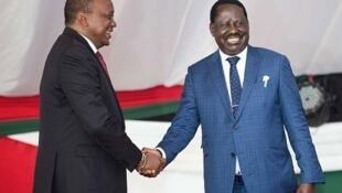 Kenyan President Uhuru Kenyatta (left) and Opposition leader Raila Odinga shake hands in a show of harmony during the annual prayer breakfast in Nairobi on May 31, 2018