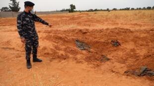 Un membre des forces de sécurité loyales au gouvernement d'union nationale montre l'emplacement d'un charnier, le 11 juin 2020 à Tarhouna.