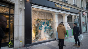 People stand in front of a damaged Tara Jarmon shop after a demonstration by the yellow vest movement on the Champs-Elysées in Paris.