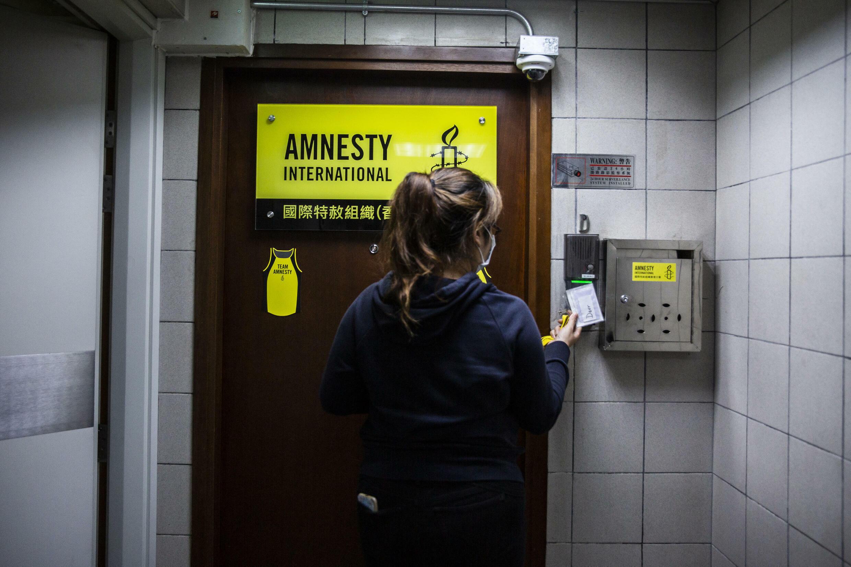 Una mujer se dispone a entrar en la oficina de Amnistía Internacional en Hong Kong, una imagen tomada en octubre de 2021 en la ciudad china