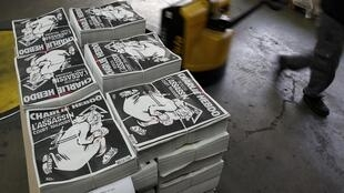 """Packed copies of the latest edition of French weekly newspaper Charlie Hebdo with the title """"One year on, The assassin still on the run"""" are seen at a printing house near Paris, France, January 4, 2016."""