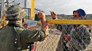 Un palestinien décline son identité à un soldat israélien derrière une barrière de séparation.