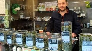 Maxime Brunet behind the counter of his CBD shop in Caen