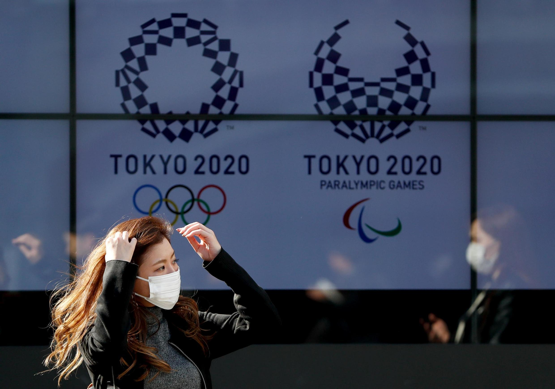 Une passante portant un masque dans les rues de Tokyo, à quatre mois de la cérémonie d'ouverture des Jeux olympiques 2020.