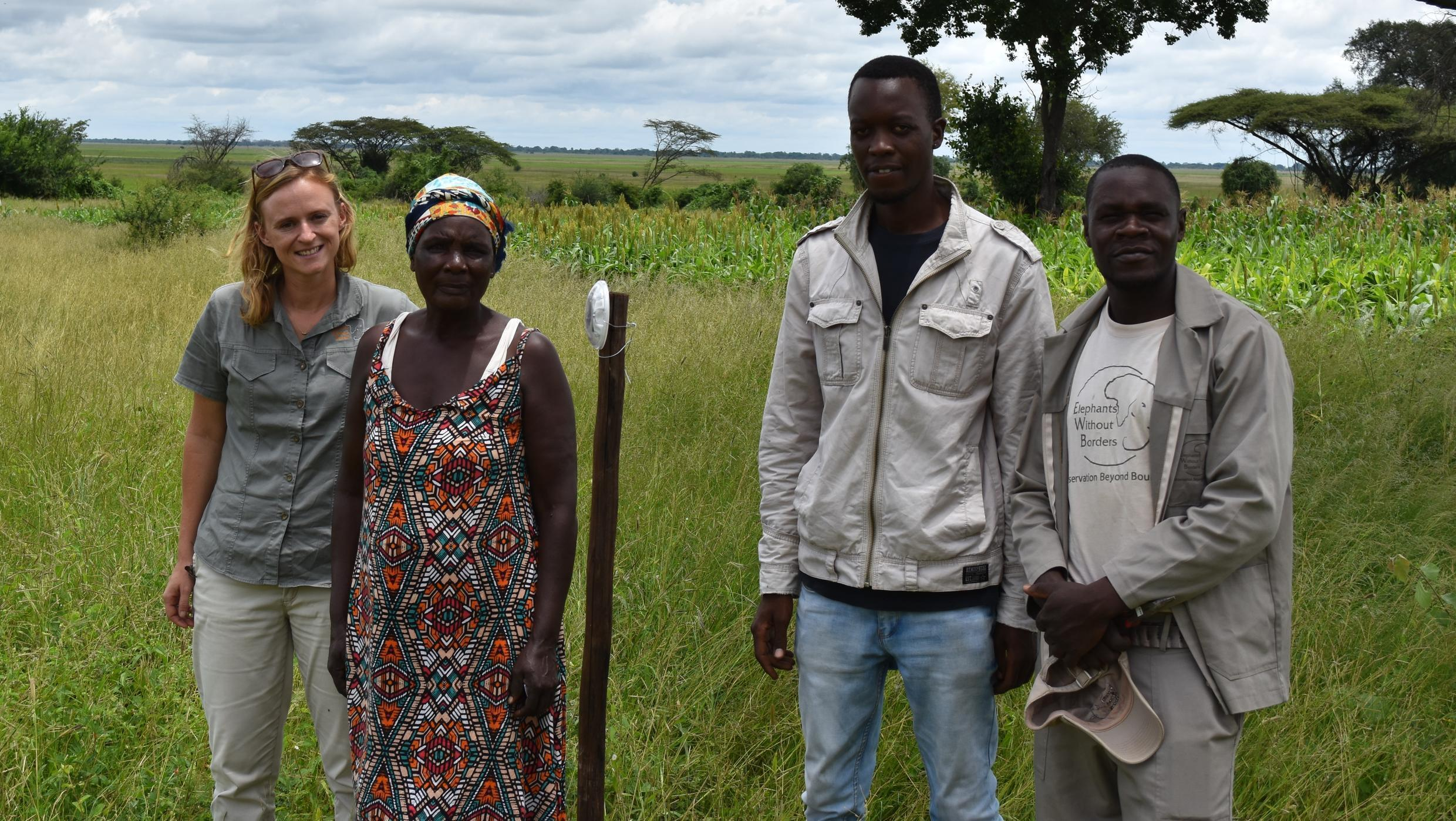 Research coordinator Tempe Adams (left) and members of the Elephants Without Borders co-existence team pose with a farmer whose maize field is protected by a strobe light barrier.