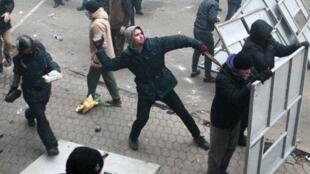 Манифестант бросает булыжник в сторону сил МВД