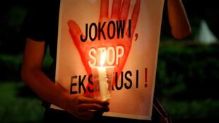 Un manifestant adresse un message au président indonésien Jokowi, l'enjoignant de stopper les exécutions capitales, lors d'une manifestation devant le palais présidentiel à Jakarta, le 28 juillet 2016.