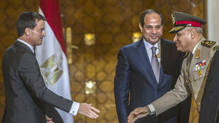 French Prime Minister Manuel Valls (L) shakes hands with Egyptian Defence minister General Sedki Sobhi (R) as Egyptian President Abdel Fattah al-Sisi (C) looks on. October 10, 2015