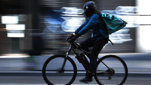 Un repartidor de la empresa Deliveroo pedalea por una calle de Madrid el 27 de marzo de 2020, durante el confinamiento general impuesto por el estado de alarma decretado a causa del coronavirus