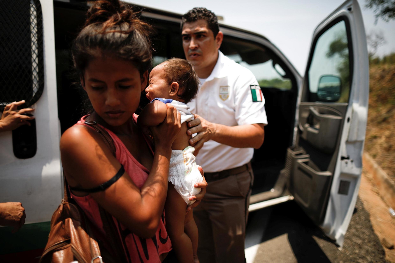 Una mujer centroamericana y su hijo están detenidos por un agente de inmigración mexicano, en Pijijiapan, el 22 de abril de 2019.