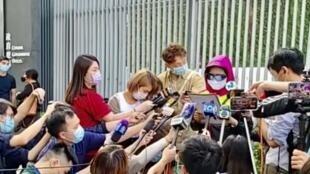 在台涉嫌遭男友陳同佳殺害的潘曉穎的母親(穿紅衣戴墨鏡),在政府總部外回答記者的問題。(網上截圖)