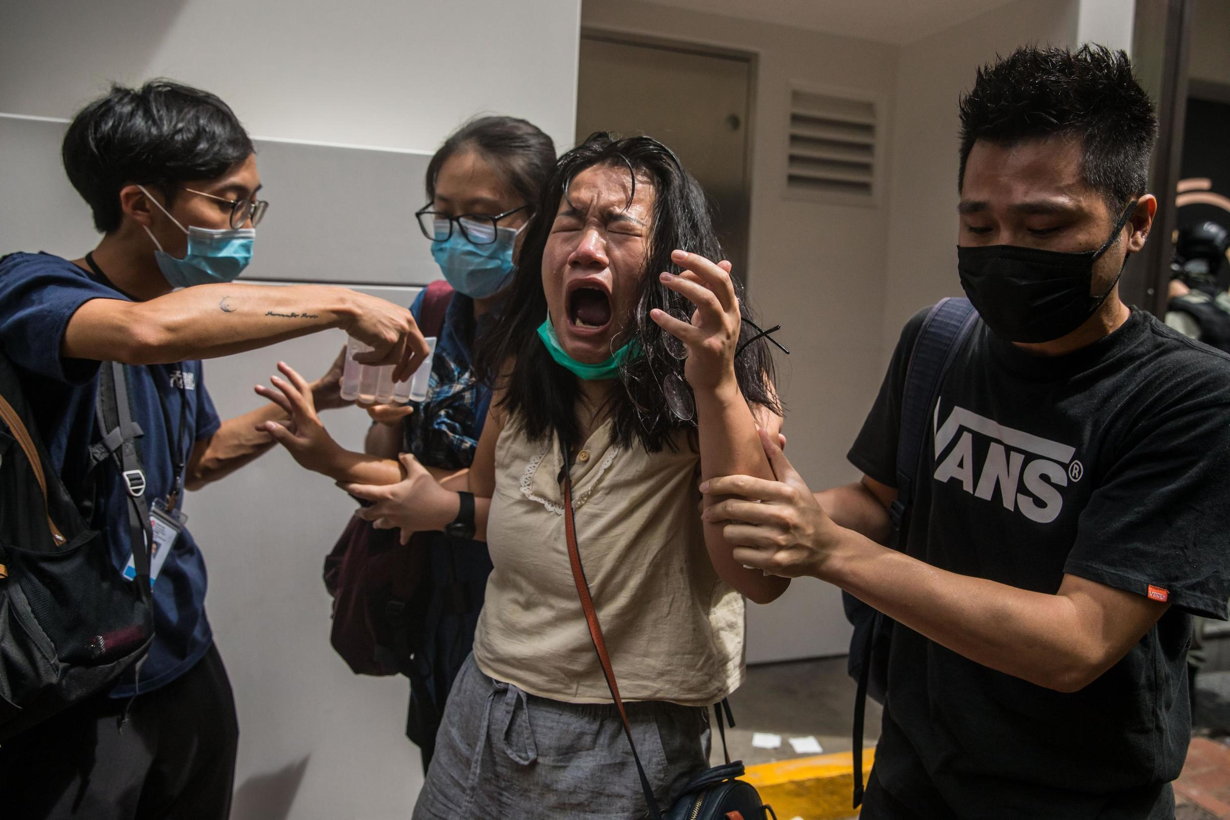 Woman reacts to tear gas sprayed by police at a pro-democracy rally in Hong Kong, on the 23rd anniversary of British handover to China. 1 July 2020.