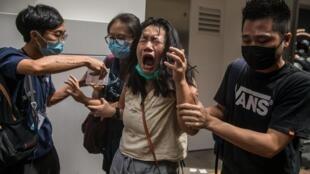 Une femme réagit au gaz lacrymogène lancé par la police contre les manifestants mobilisés contre la nouvelle loi de sécurité nationale. Hong Kong, le 1er juillet 2020.