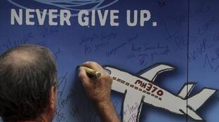 一人在纪念墙上刻记在马来西亚航空370号班机空难失踪亲人的名字   2014年3月8日