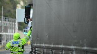 Un oficial de policía verifica la documentación de la prueba Covid-19 de un conductor de camión de carga proveniente de Francia en la entrada del puerto de Dover, sureste de Inglaterra, el 1 de enero de 2021