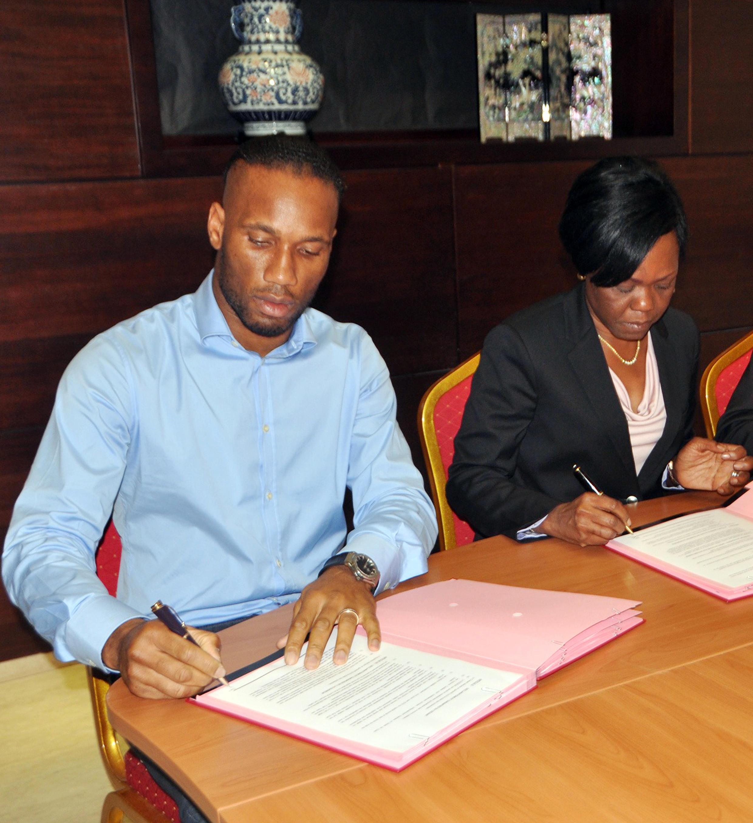 Didier Drogba (G) et Niale Kaba, la ministre de l'Economie et des Finances, signent le 7 janvier 2014 les documents qui officialisent l'acquisition par le fotballeur ivoirien de 5% du capital de la mine d'or d'Ity, en Côte d'Ivoire.