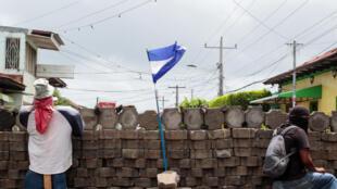 Manifestantes atrás de uma barricada na Nicarágua