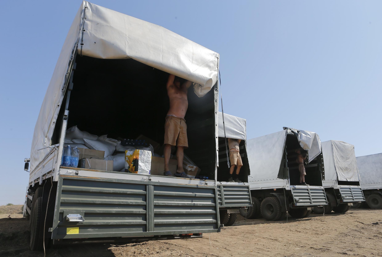 Russos abrem caminhões para mostrar carregamentos para autoridades ucranianas.