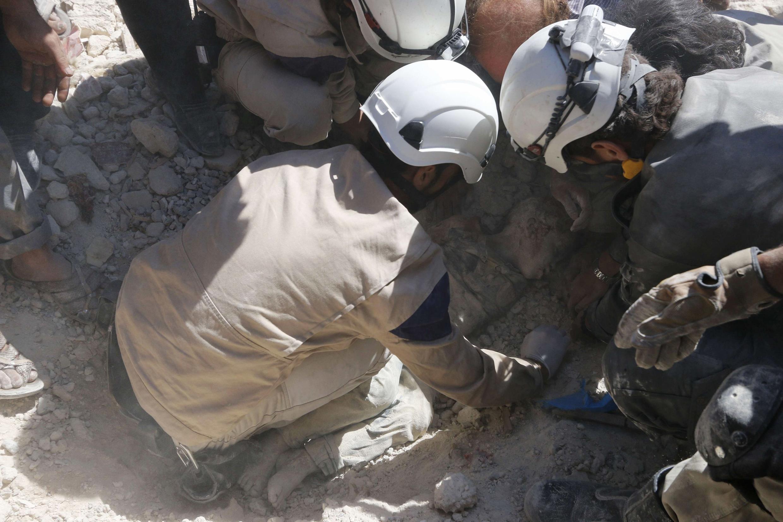 Des Casques blancs dans la région d'Alep sortent des corps des décombres après un bombardement, le 30 septembre 2014.