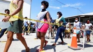 Des employées marchent à une distance de sécurité les unes des autres lors d'une pause chez un fabricant de vêtements local, qui fabrique désormais des masques de protection, à Port-au-Prince, le 21 avril 2020.