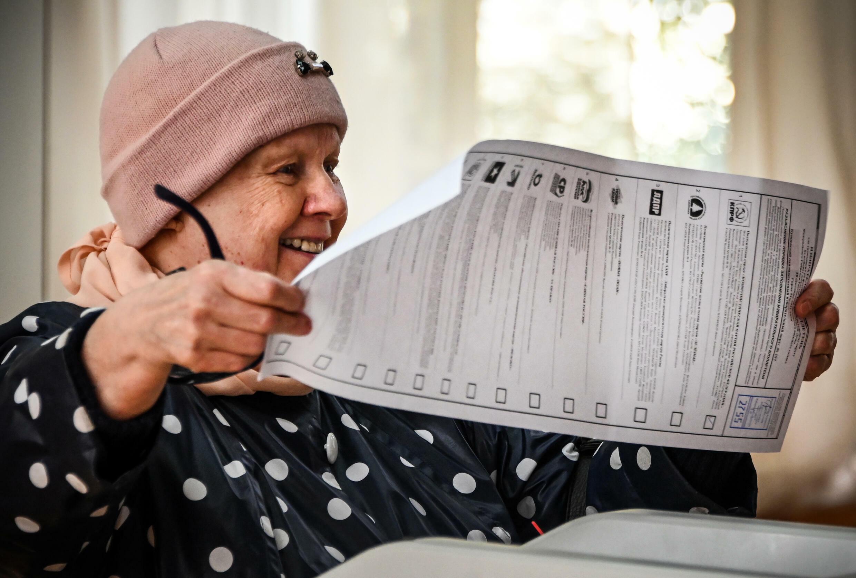 Una mujer mira una papeleta para votar en las elecciones legislatvas rusas, en Moscú el 18 de septiembre de 2021