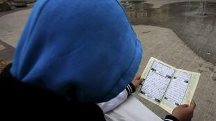 A teenager reads the Koran in Paris March 31, 2012