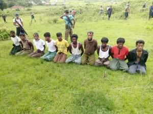 Rohingya Muslim men with their hands bound kneel as members of the Myanmar security forces stand guard in Inn Din village, 2 September 2017.